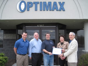 Finger Lakes Workforce Investment Board Executive Director, Karen Springmeier, presenting Optimax Systems, Inc. with the certificate for the Business of the Month.