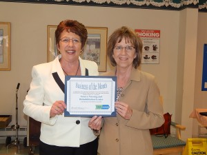 Karen Springmeier, Executive Director at Finger Lakes Workforce Investment Board, presents Mary Lee Burnell, Seneca Nursing and Rehabiliation Center Administrator, with the Business of the Month award for June.