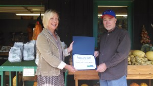 Loree Martin, Yates County Youth Counselor presents the award to Lonnie Jones, Owner of Indian Pines Farm Market.