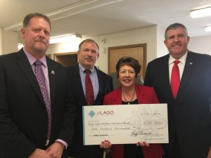 Karen Springmeier poses with the check and three FLWIB Members, (l-r) Mike Davis, Scott Bischoping (WFL BOCES), and Michael Rusinko (Lyons National Bank).